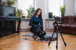 Caucasian female athlete in sportswear poses on floor preparing her equipment with photocamera in apartment.