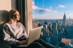 Caucasian female digital nomad sitting with laptop computer on window sill of modern skyscraper building coworking. Young woman freelancer enjoying downtown cityscape from hotel room during vacations