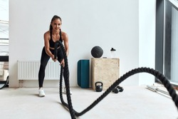 Caucasian female doing crossfit exercises using rope. Young beautiful woman in sportswear. Background light fitness studio