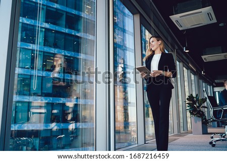 Caucasian female entrepreneur dressed in formal wear going near panoramic window in office, confident business woman with modern digital tablet looking away during working day in enterprise