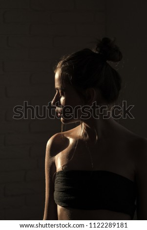 Caucasian female fashion model posing. Woman with hair, bun, sensual face and bare shoulders. Girl with oily or wet skin on dark background. Purity, perfection, sensuality concept. Beauty, fashion #1122289181