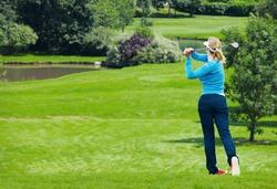 Caucasian female golfer hit a golf ball by golf-club driver