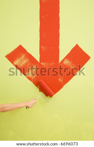 Caucasian female hand painting red downwards arrow on wall.