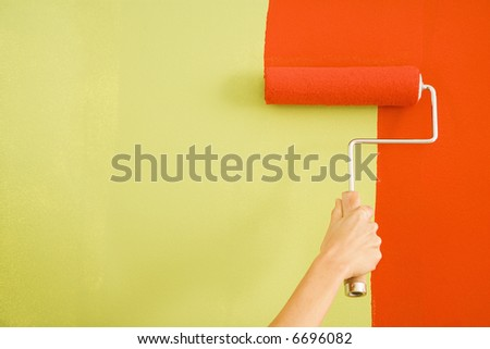 Caucasian female hand painting red over a green wall with a paint roller.