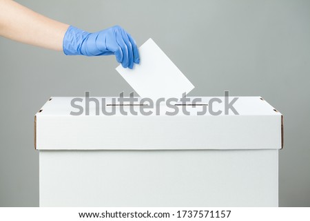 Caucasian female hand wearing blue protective latex rubber glove placing ballot paper in vote box, side view, prevention of spread and transfer of Coronavirus at the voting place, COVID-19 pandemic