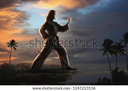 Caucasian female in kimono practicing taekwondo. Modern Korean martial art similar to karate