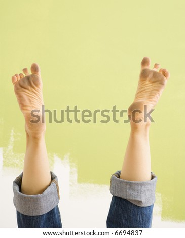 Caucasian female legs and dirty feet sticking up in air.