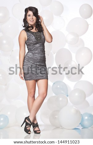 Caucasian female posing in a grey cocktail dress in front of a white and blue balloon wall.