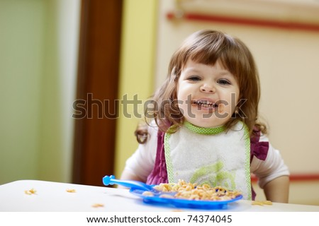caucasian female preschooler eating pasta and smiling at camera. Horizontal shape, waist up, front view - stock photo