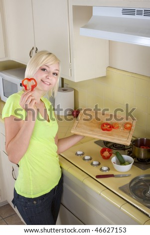 Caucasian female presenting tomatoes and lettuce holding in hands by kitchen stove range