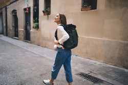 Caucasian female tourist with travel backpack walking around historic quarter enjoying solo vacations, casual dressed woman 30 years old exploring city streets during international excursion in town