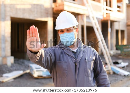 Caucasian foreman wearing mask and hardhat at construction site, building in background. Concept of coronavirus social distance and covid-19.