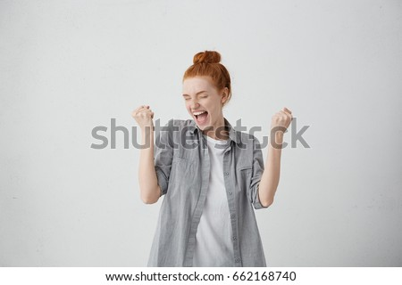 Caucasian freckled woman with red hair rejoicing her success and victory clenching her fists with joy. Lucky woman with hair bun being happy to achieve her aim and goals. Positive emotions, feelings