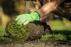 Caucasian Gardener Installing Natural Grass Turfs in Garden. Close Up Photo. Natural Grass is the Best Thing to Install to Maintain the Ecosystem of Your Home. Landscaping Industry Photo.