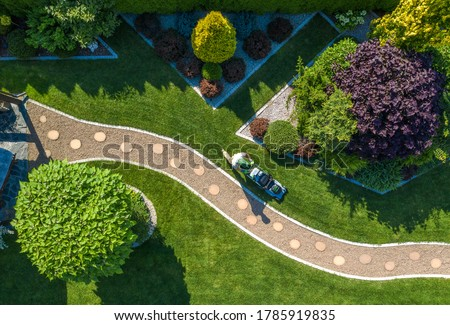 Caucasian Gardener with Grass Mower Trimming Beautiful Backyard Garden Lawn. Aerial View. Gardening and Landscaping Industry.
