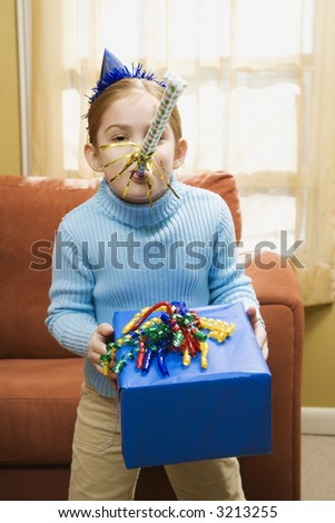 Caucasian girl blowing noisemaker and holding gift.
