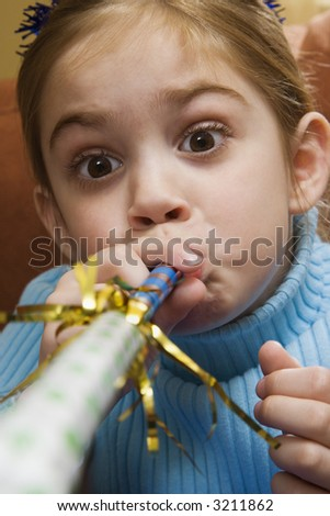 Caucasian girl blowing noisemaker and making facial expression.