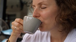 Caucasian girl enjoys a sip of hot vegan cappuccino. Simple pleasures concept.