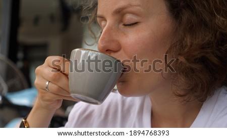 Caucasian girl enjoys a sip of hot vegan cappuccino. Simple pleasures concept. Stock photo ©