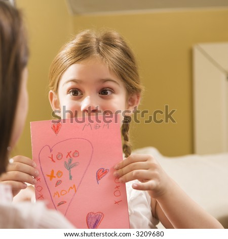 Caucasian girl giving mid adult mother a drawing.