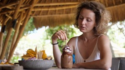 Caucasian girl having lunch alone in a beach restaurant, looks behind her shoulder. Travelling solo concept