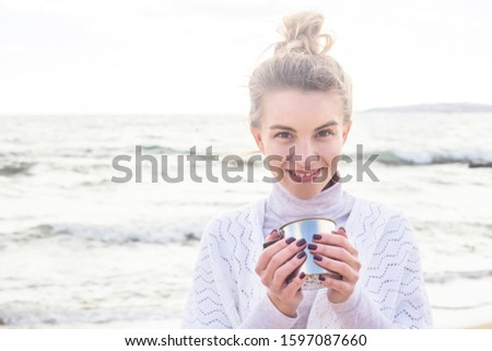 Caucasian girl in a white boho jacket with a bunch on her head and a metal cup in her hand by the sea on a windy day. Traveling in nature.