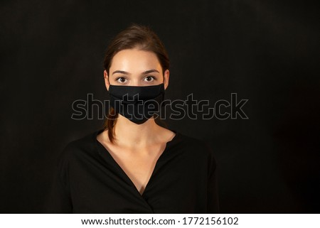Caucasian girl in black clothes and face protection facing the camera in front of a black backdrop. Studio portrait of a young woman on dark background with copyspace for text.