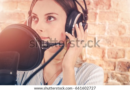 Caucasian Girl in Her 20s in the Audio Recording Studio. Recording Voice.