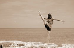 caucasian girl performing rhythmic gymnastics exercises with the leg up and the foot over the head by the sea with Sepia Effect