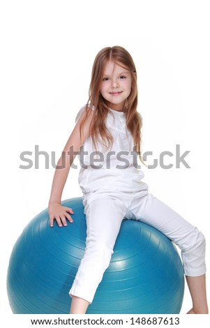 Caucasian girl playing sports on fitball on white background