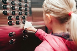 Caucasian girl pushing elevator button with disinfecting wet wipe. Precaution against virus spread. COVID-19 coronavirus danger and fast epidemic virus contagion concept.