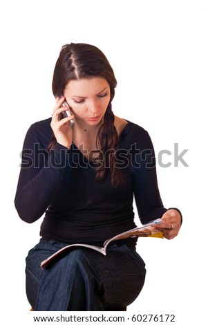Caucasian girl reading magazine and talking by mobile phone. Isolated on white.