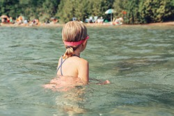Caucasian girl swimming in lake river with underwater goggles. Child diving in water on beach. Authentic real lifestyle happy childhood. Summer fun outdoor aquatic activity. View from back.