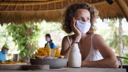 Caucasian girl takes off her protective face mask to try whipped cream of her milkshake during lunch at a outdoor restaurant.