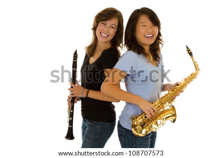 Caucasian girl with a clarinet and with an Asian girl with a gold saxophone. - stock photo