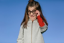 Caucasian girl with round nerd glasses, with ugly and unpleasant expression. In a sky background. children and students concept.
