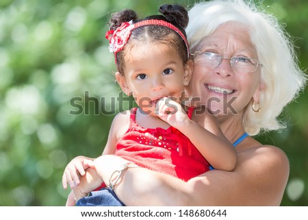 Caucasian grandmother carrying her small latin granddaughter