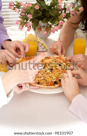 Caucasian group of four people with pizza and juice sitting in a cafe