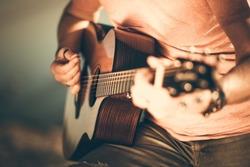 Caucasian Guitarist Playing Acoustic Guitar. Closeup Music String Instrument Theme.