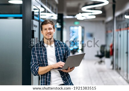 Caucasian guy freelancer with laptop. A successful guy dressed in stylish casual wear stands in a creative office, holds a laptop, looks and smiles friendly at the camera Stock photo ©