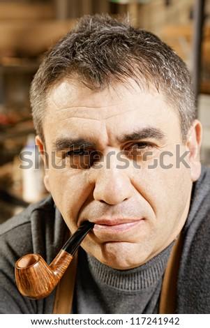 Caucasian guy smoking pipe in workshop