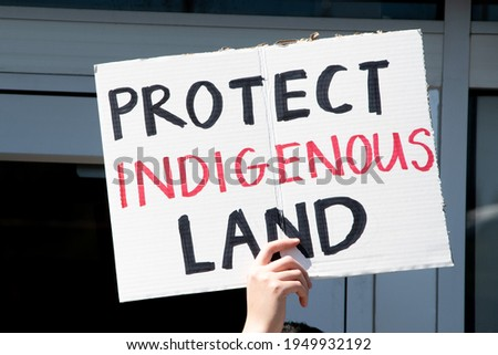 Caucasian hand holding sign reading 'Protect Indigenous Land' at a protest in response to fossil fuel pipelines being routed through protected Native American reservations and danger of polluted water Photo stock ©