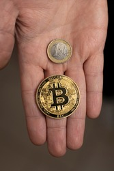 Caucasian hand shows one Bitcoin coin and one Euro Coin. New finance concept. Comparison between currencies, fiat and crypto. One hand