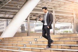 Caucasian handsome businessman confidently walking down the stairways while using the smartphone, wearing black suit and tie with city skylines and urban architectural structure in the background