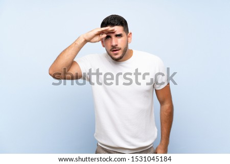 Caucasian handsome man over isolated blue background looking far away with hand to look something