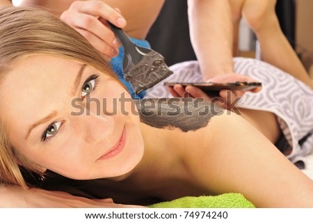 Caucasian handsome spa woman getting wellbeing massage laying on green towel. Copyspace