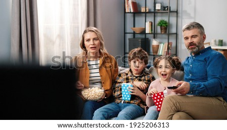 Caucasian happy cute Caucasian family spending time at home watching TV sitting on sofa with popcorn and shocked amazed faces. Parents with small children eating popcorn watching movie or cartoon