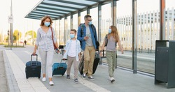 Caucasian happy family with two cute small kids walking at bus stop or train station, carrying suitcases on wheels and talking. Parents with little daughter and son in medical masks travelling.