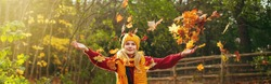 Caucasian happy smiling woman girl in warm yellow scarf and hat throwing autumn fall orange red leaves in park forest outdoor. Seasonal activity lifestyle outside. Web banner header for website.