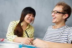Caucasian happy young man talking with a Chinese girl is language teacher